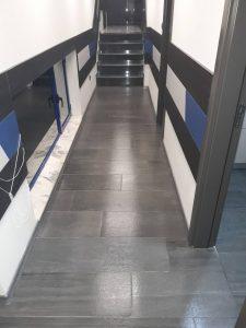 Почистен коридор с прозорци и стълби.