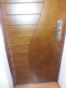 Покрита със строителен праз и боя входна врата.