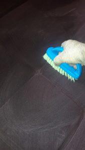Разнасяне на перилен препарат по тапицерия на диван.