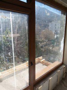 Прозорец с налепи от мазилка и строителен прах.