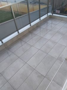 Почистен гранитогрес и стъклена ограда на тераса.