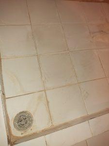 Замърсени с варовик плочки на баня.