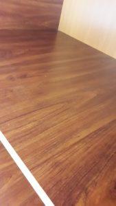 Почистен дървен рафт в офис помещение.