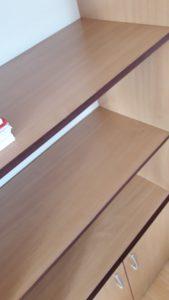 Почистени и дезинфектирани дървени рафтове в офис.