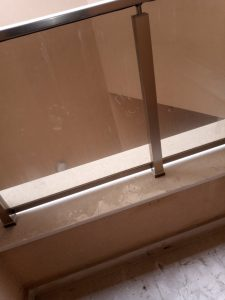 Замърсено стъклено заграждение на тераса.